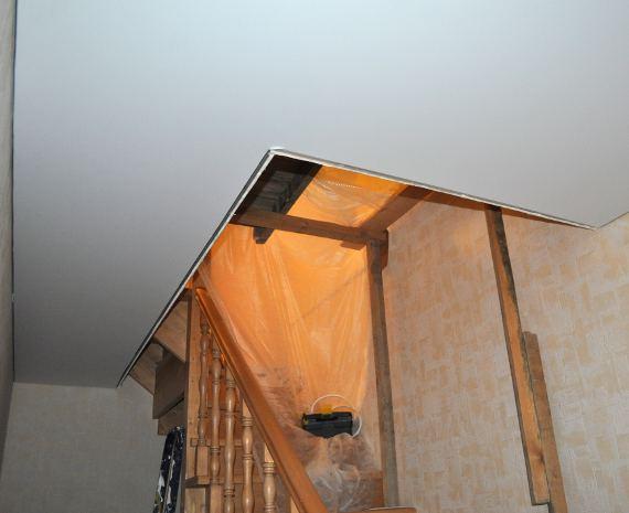 Готовый натяжной потолок в проеме лестницы